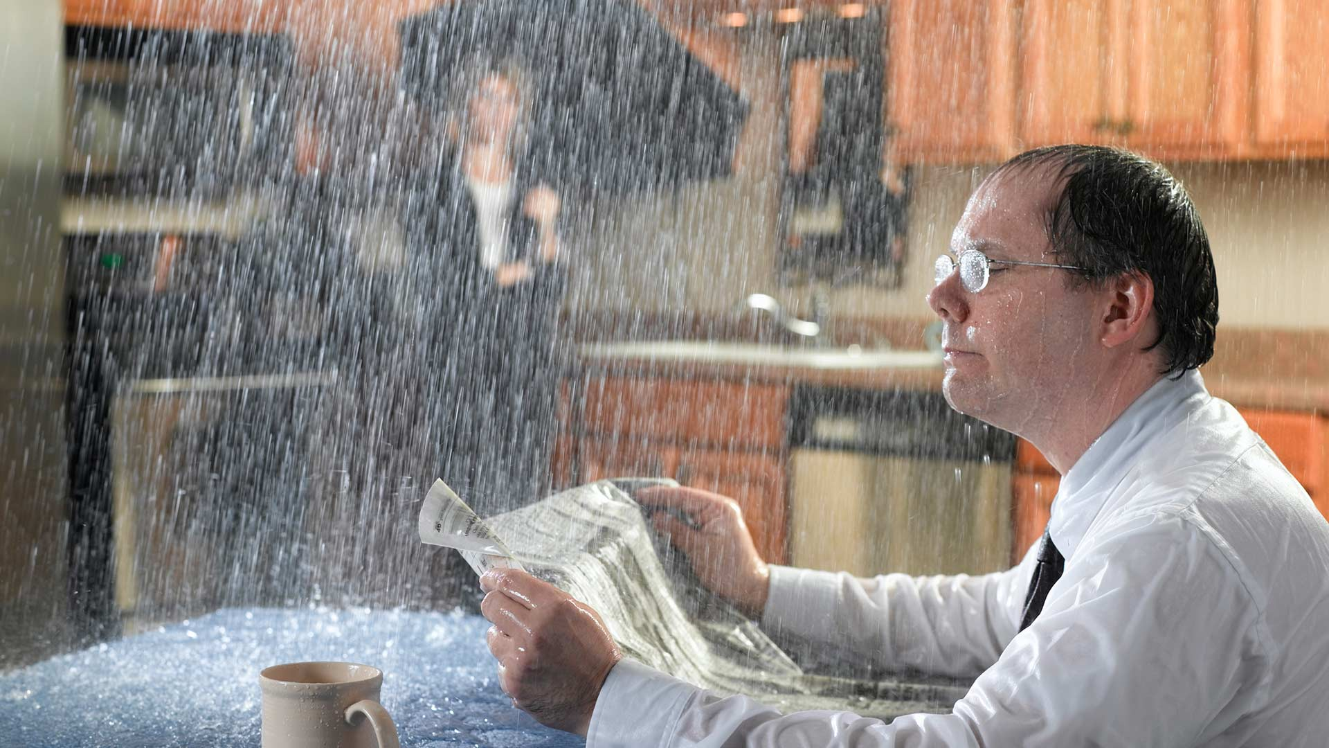 man reading newspaper in kitchen with rain